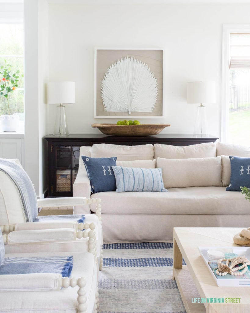 Oversized shadow box art with a palm frond in a coastal decorated living room.