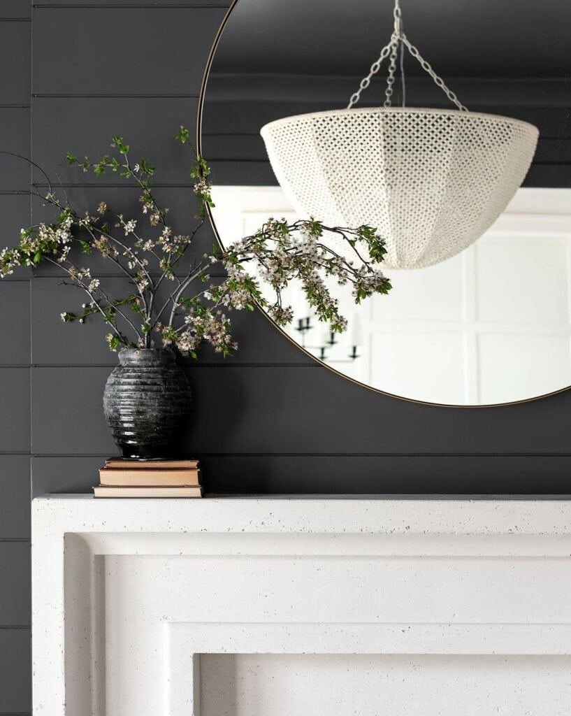 A weathered charcoal vase filled with fresh branches, styled on a limestone fireplace with black shiplap, a round mirror and white chandelier.