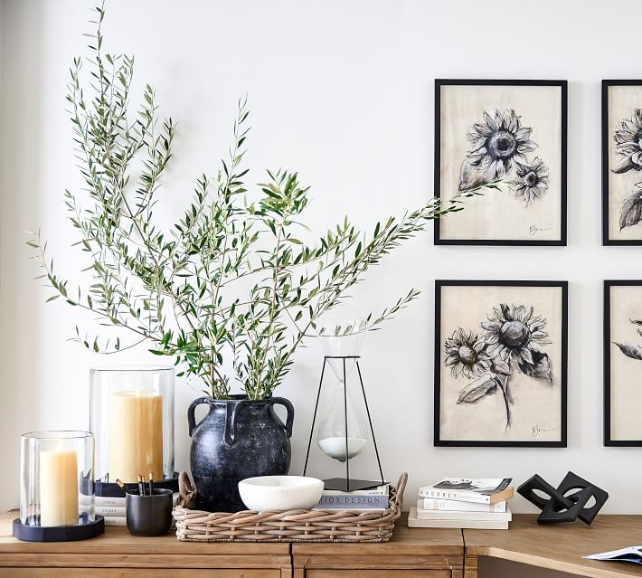 A beautiful weathered black vase filled with olive branches. Also shown are pillar candles and sunflower art styled on a desk.