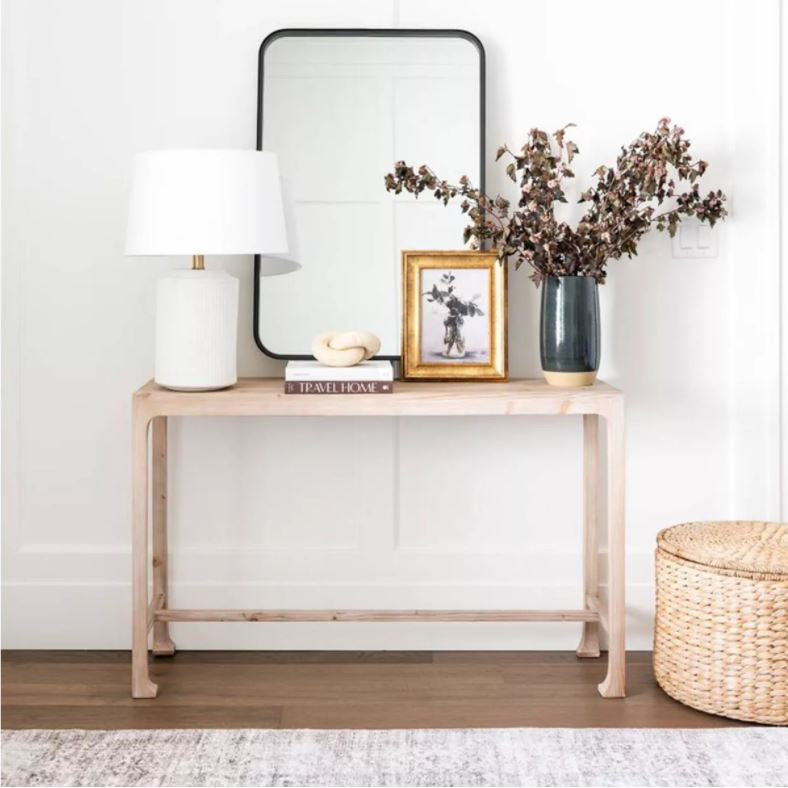 A natural wood console table styled with a white ceramic lamp, tall metal mirror, limestone knot decor, gold framed art, and a dark charcoal vase filled with fall leaves.
