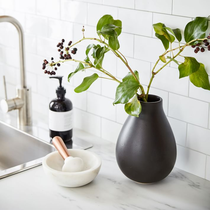A matte black ceramic vase holding fresh greenery. Styled in a kitchen with marble countertops and white subway tile.