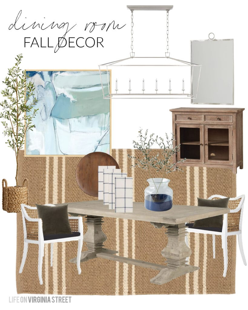 Dining room decor for fall including a faux olive tree, olive leaf stems, plaid napkins, and dark wood chargers. Also includes oversized blue abstract art, a camel color striped rug, reclaimed wood dining table and cane dining chairs.