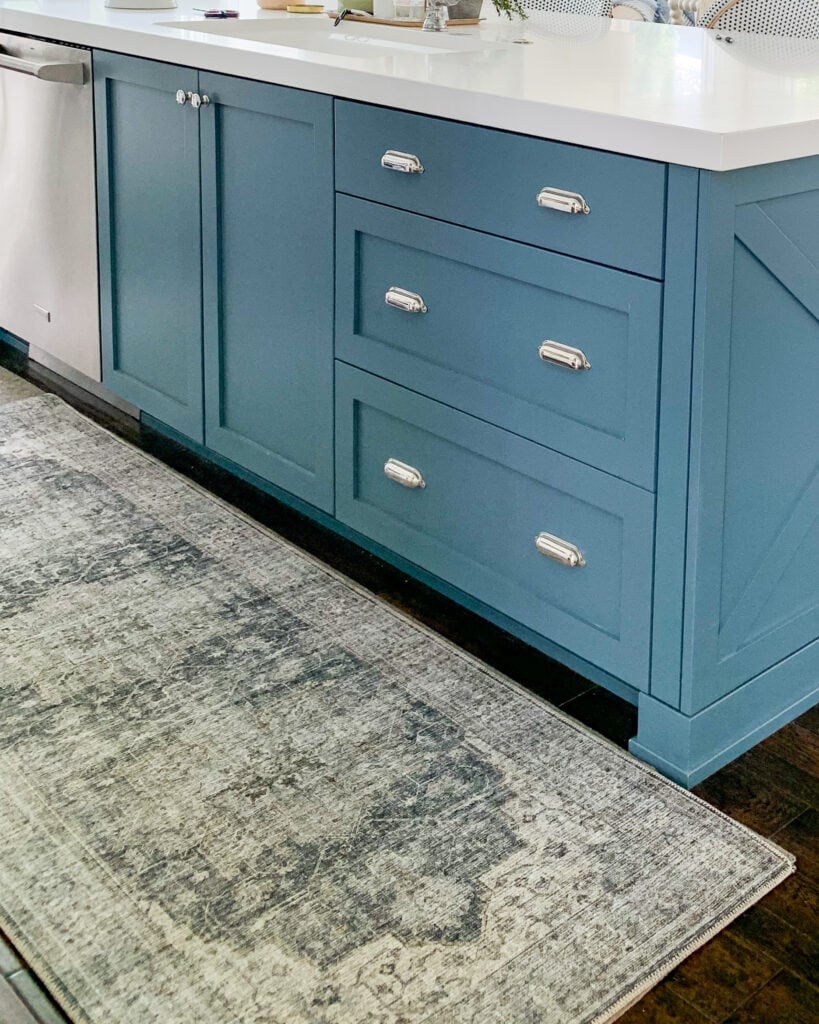 A blue kitchen island with silver bin pulls and a vintage style runner rug.