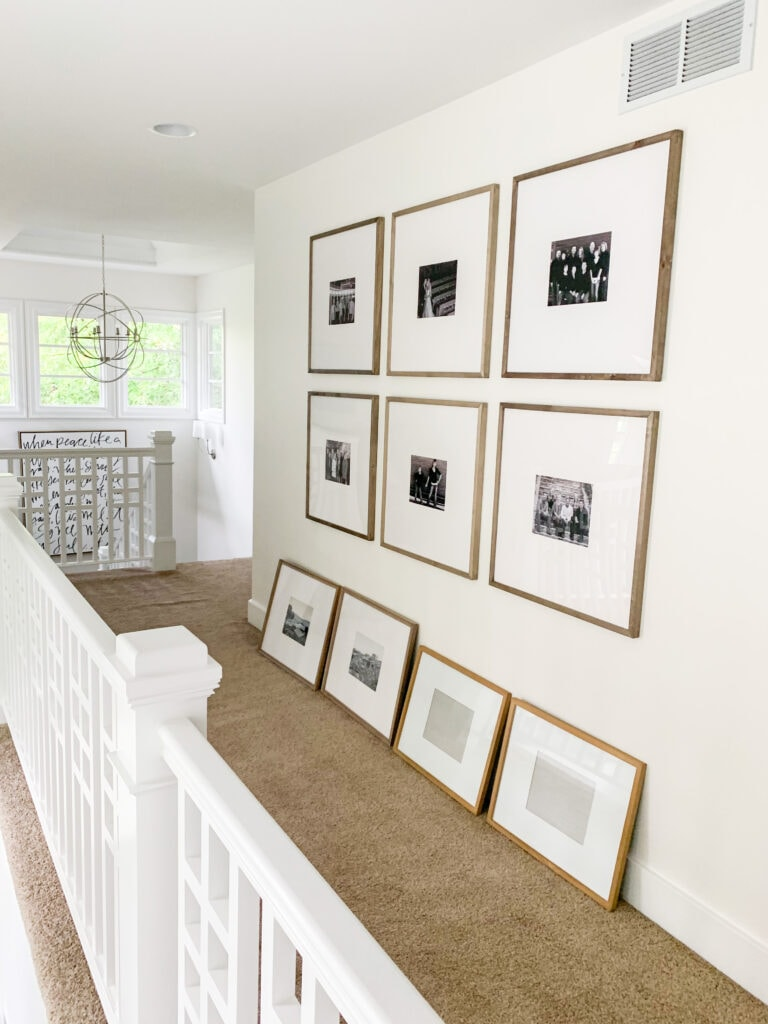 A hallway with white walls and an orb chandelier displaying various wood gallery wall frames for photo gallery walls.