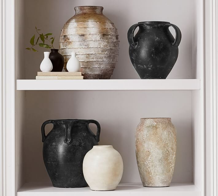 A collection of weathered vases styled on a bookshelf.