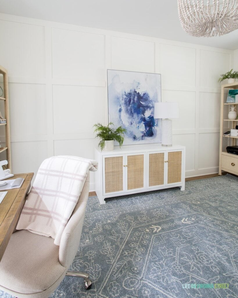 Home office with white board and batten grid wall, slate blue patterned rug, white and cane credenza, blue abstract art and linen desk chairs.