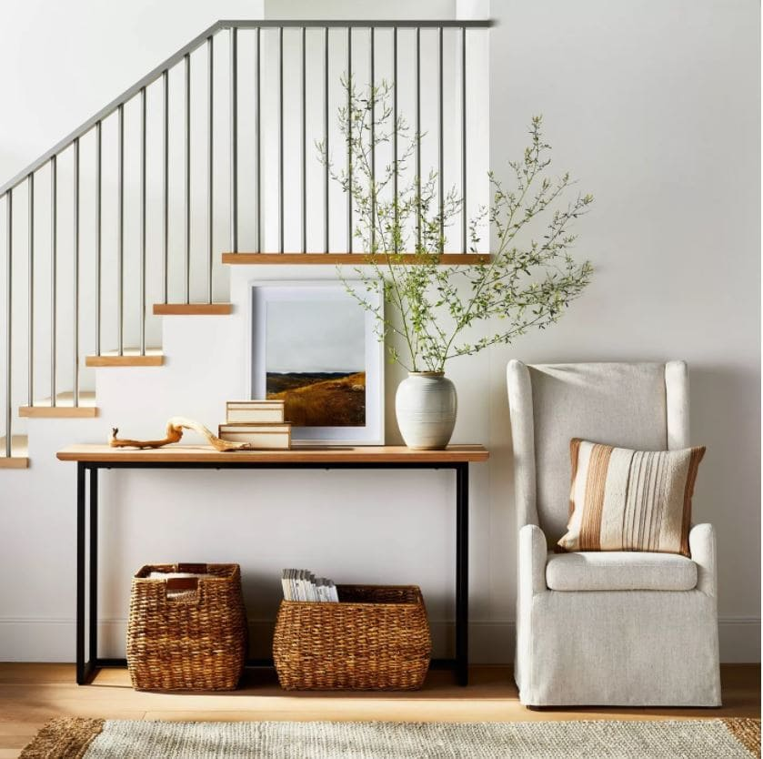 An entryway decorated for fall with a wood and iron console table, upholstered armchair, ceramic vase, woven baskets, landscape art, and ceramic vase with large branches. All from the new Studio McGee fall collection at Target!