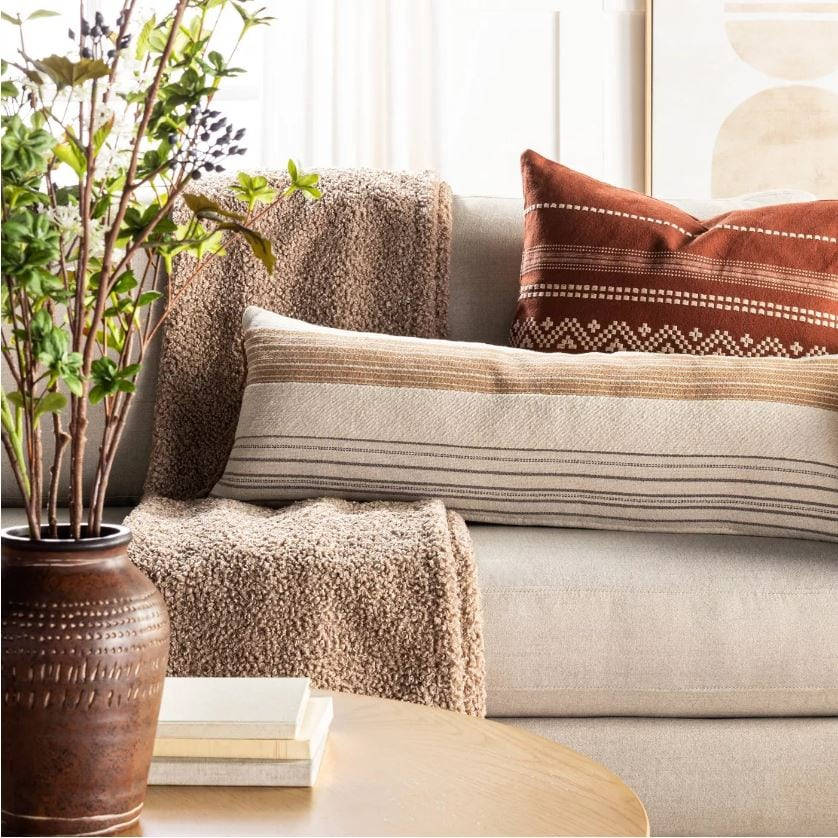 A cozy fall sofa filled with a boucle throw blanket, oversized striped lumbar pilllow, and embroidered pillow and abstract wall art in the background.