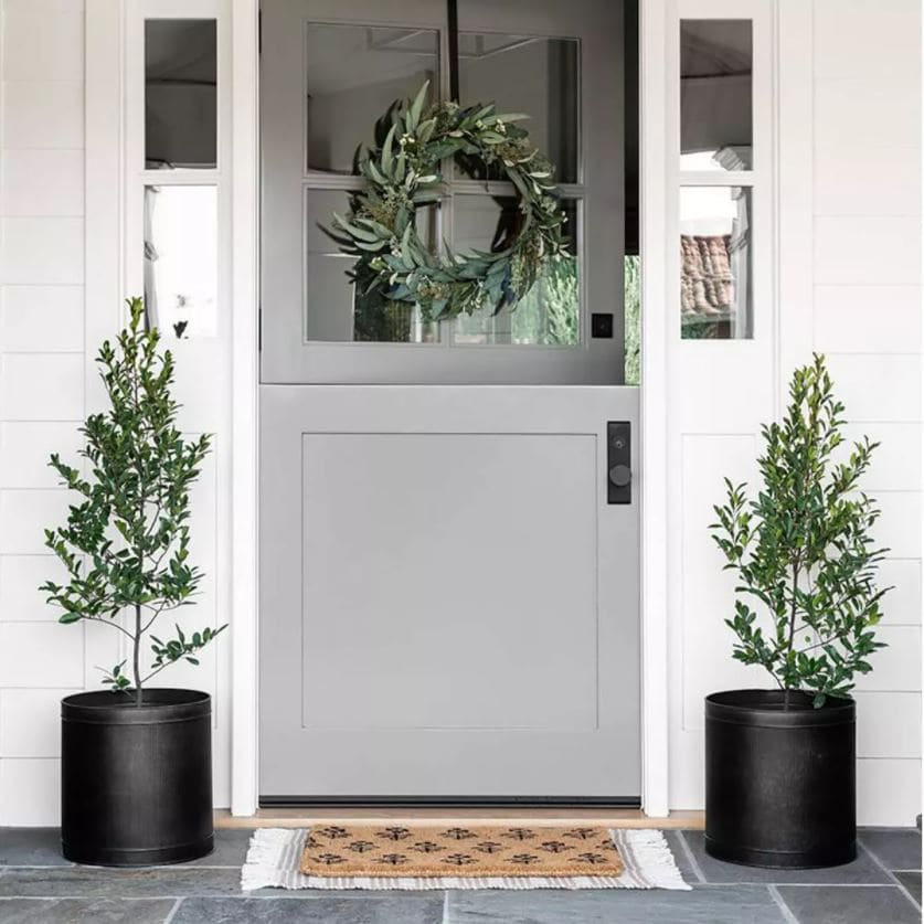 A cute front porch with gray Dutch door, black planters, faux eucalyptus wreath, block print doormat and a striped outdoor rug.