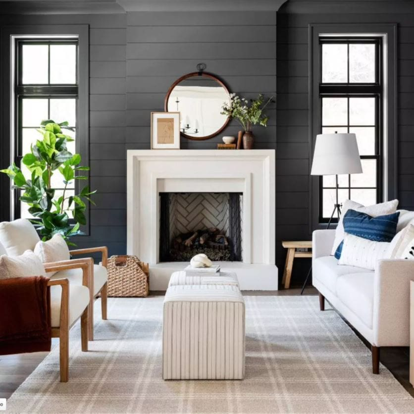 Some of the best finds from the w Studio McGee fall collection at Target! Shown here in a moody living room with dark shiplap, tan plaid rug, striped ottoman cubes, a round mirror over the fireplace with leaning art, wood and upholstery chairs, a faux rubber tree, and an oversized tripod lamp.