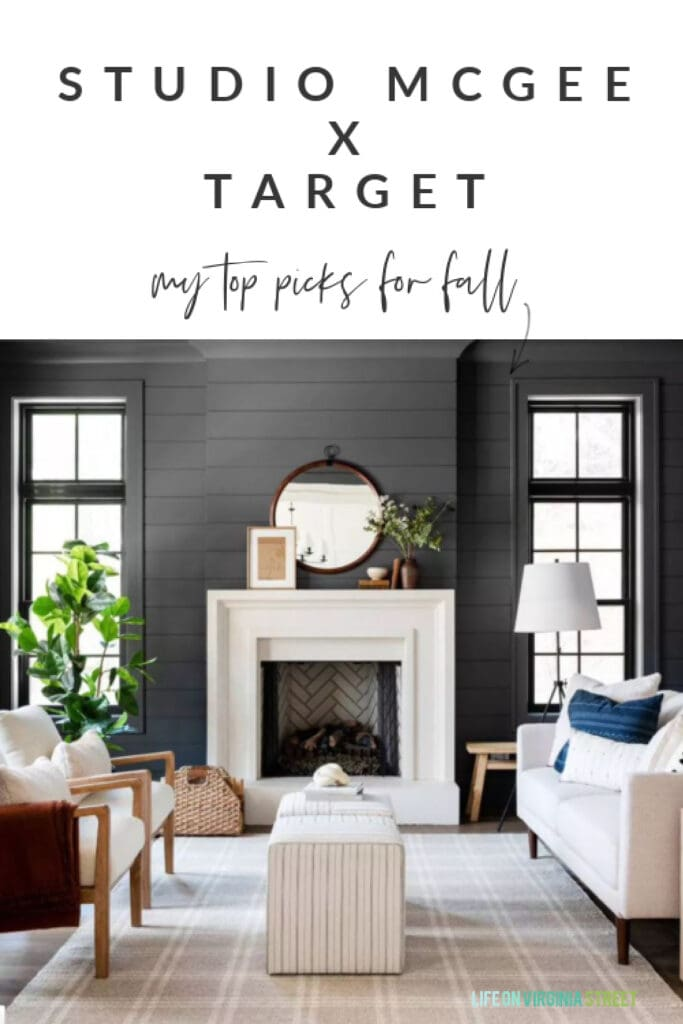 A dark shiplap living room with tan plaid rug, striped ottoman cubes, a round mirror over the fireplace, wood and upholstery chairs, a faux rubber tree, and an oversized tripod lamp.