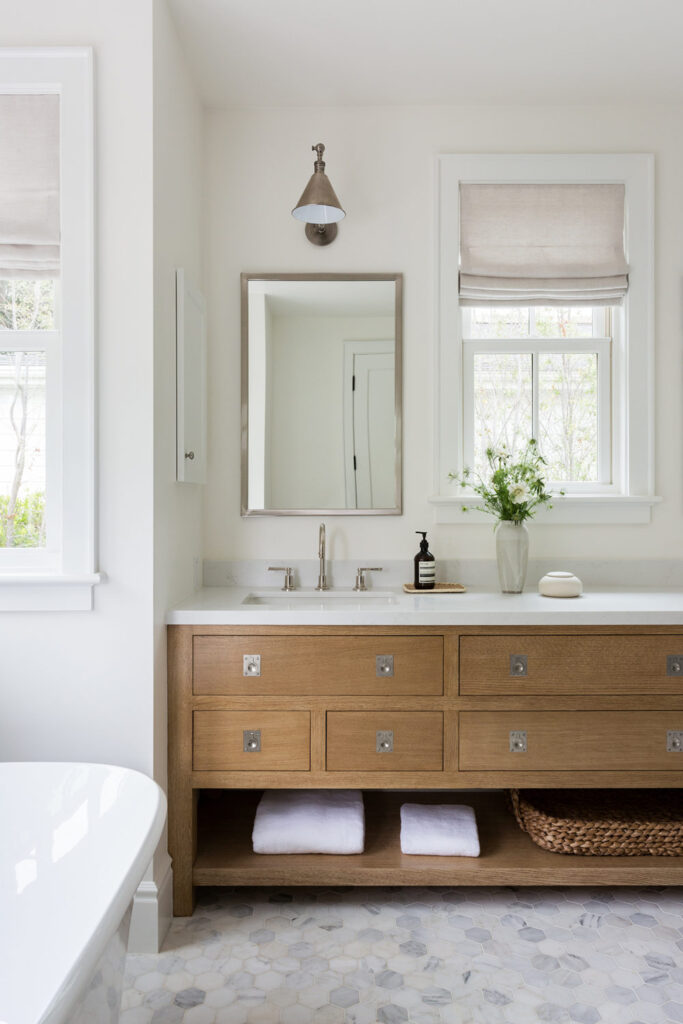 A beautiful bathroom with a long wood vanity, marble hex tile floors, a large tub, and windows with linen roman shades.