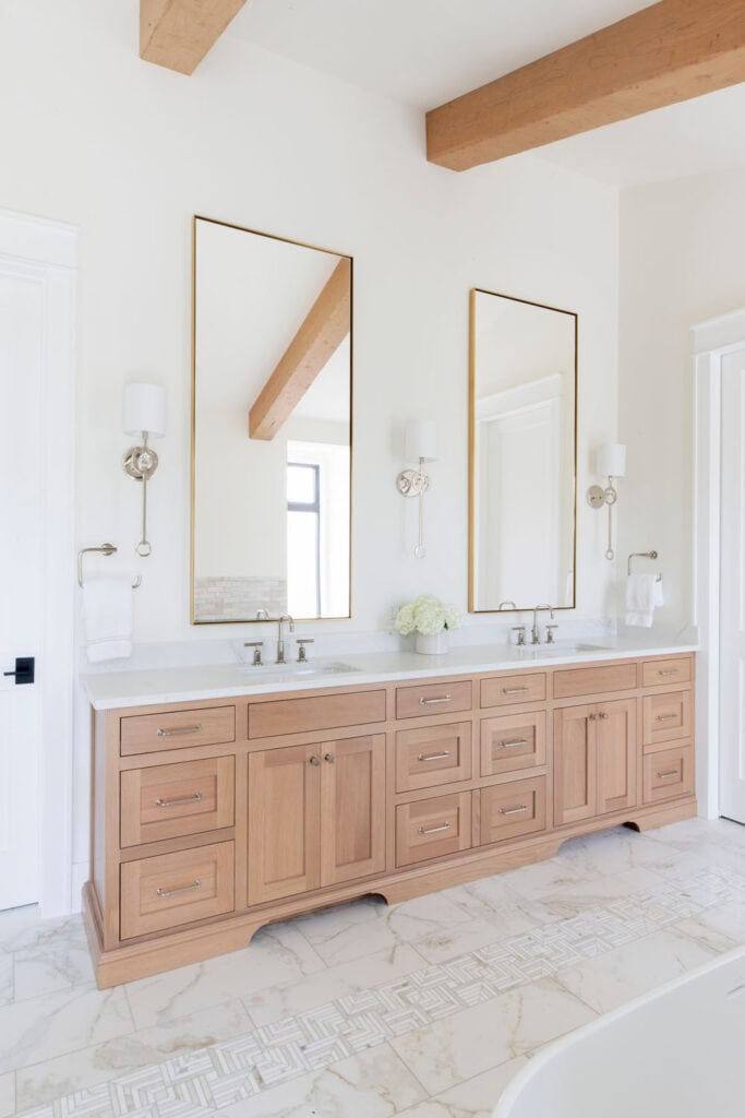 A large wood vanity in a bathroom with white walls, marble floors, wood beams, and tall brass mirrors.