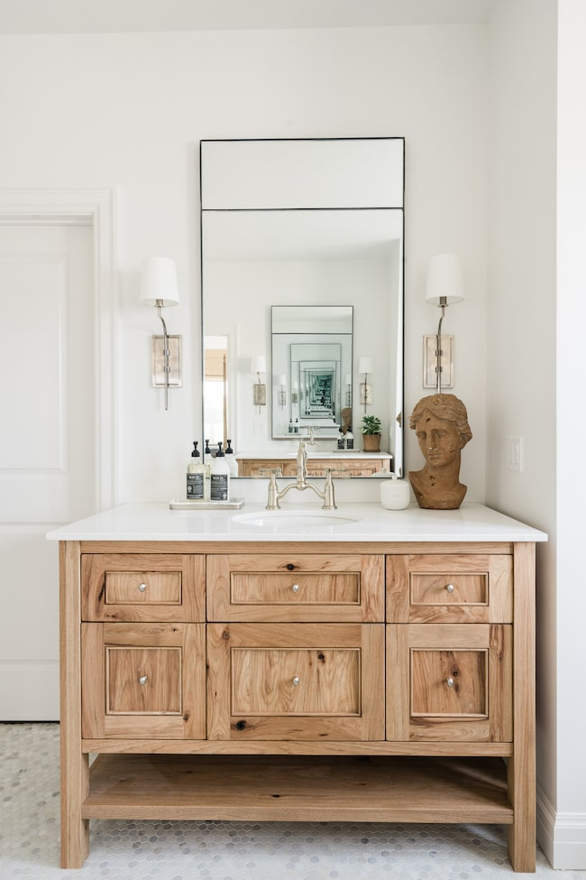 Loving these small bathroom ideas, including this wood vanity, small hex marble tile floors, silver sconce lights, and a tall thin black frame mirror.