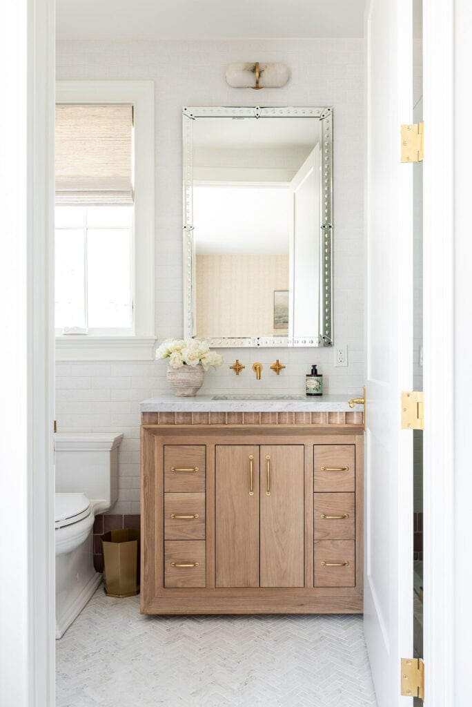 A cute girls' small bathroom ideas with herringbone marble floor, a fluted wood vanity, tall mirror, and a window over the toilet with a roman shade.