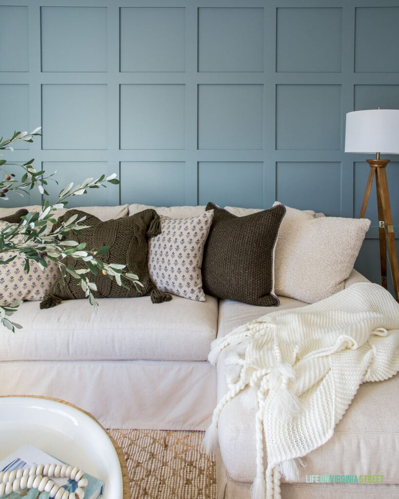 A moody board and batten grid wall (painted Benjamin Moore Van Courtland Blue) in a den with linen sectional, wood tripod lamp, and cozy pillows.