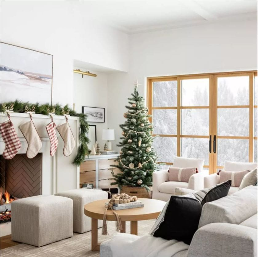 A beautiful living room with white walls, large wood sliding doors and white limestone fireplace. Decorated with the new Studio McGee x Threshold Christmas collection at Target.