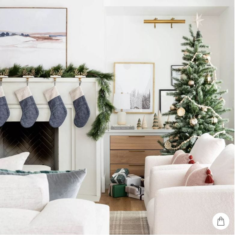 A beautiful white living room with garland on the white limestone mantel, with abstract art, blue colorblock stockings, a plaid rug and Christmas tree with metallic ornaments.