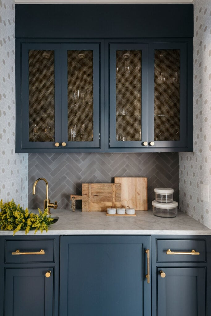 Tudor house renovation ideas like these navy blue cabinets with gold mesh insert in cabinet doors. Perfect for a butler's pantry!