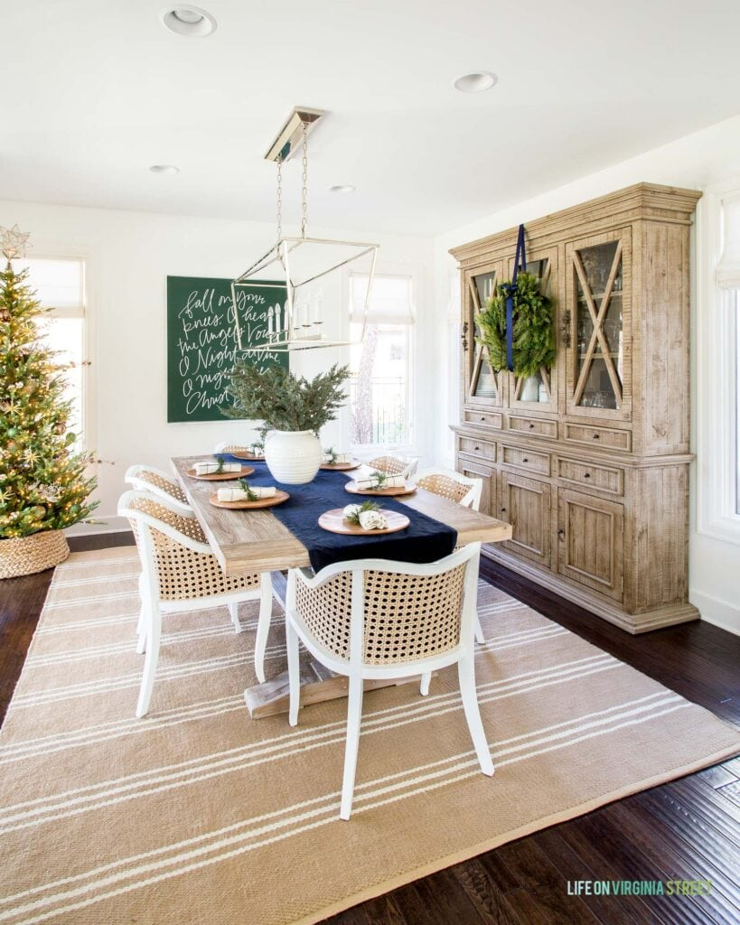A neutral dining room decorated for Christmas with large carol artwork, a wreath, faux Christmas tree, navy blue table runner, and cane dining chairs.