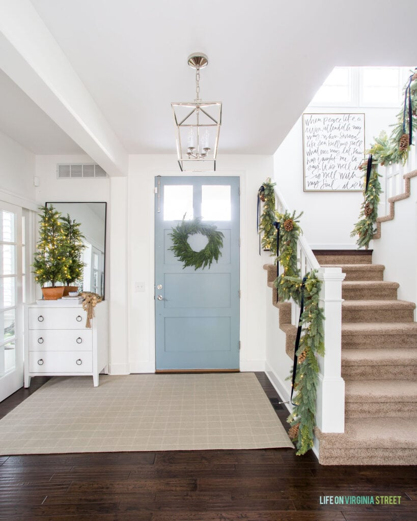 An entryway with white walls, blue gray front door, and plaid rug, decorated for Christmas with garland on the staircase and a wreath on the door.