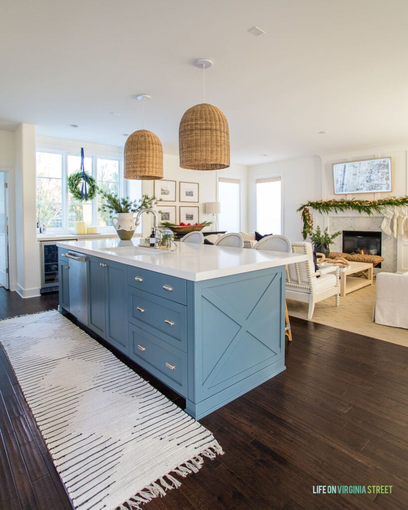 Our 2020 Christmas home tour featuring our kitchen with a blue island, ivory and black runner rug, basket pendant lights, and a wreath on the window.