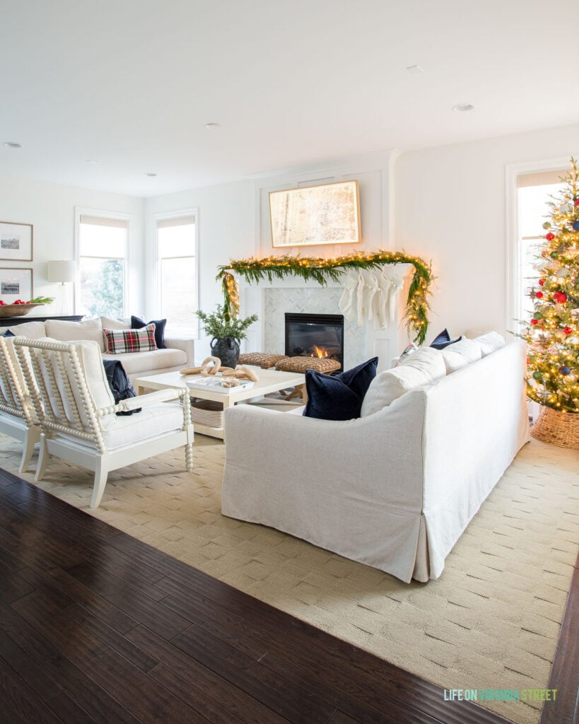 A white living room decorated for Christmas with a Christmas tree, navy blue and red ornaments, garland on the mantel with ivory stockings, and Stewart plaid pillows.