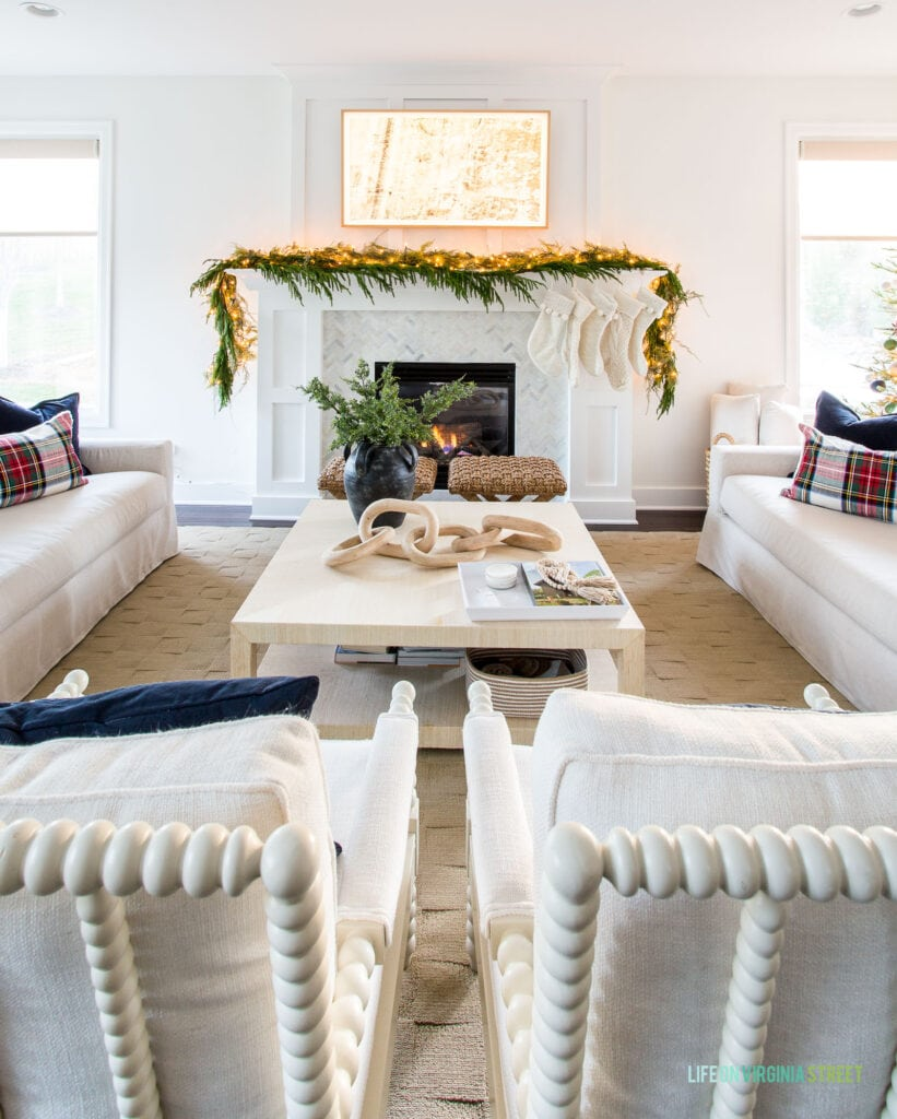A Frame TV hanging over a Christmas mantel with ivory stockings and garland. You can also see a raffia coffee table, white spindle chairs and linen sofas with navy blue velvet and plaid pillows.