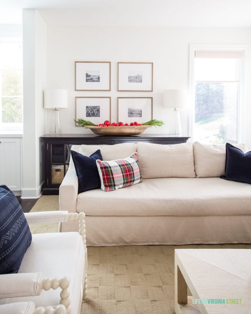 A linen sofa with navy blue velvet pillow, plaid lumbar pillow, a black console cabinet, wood gallery wall frames, and a wood dough bowl filled with bright red ornaments and faux evergreens.