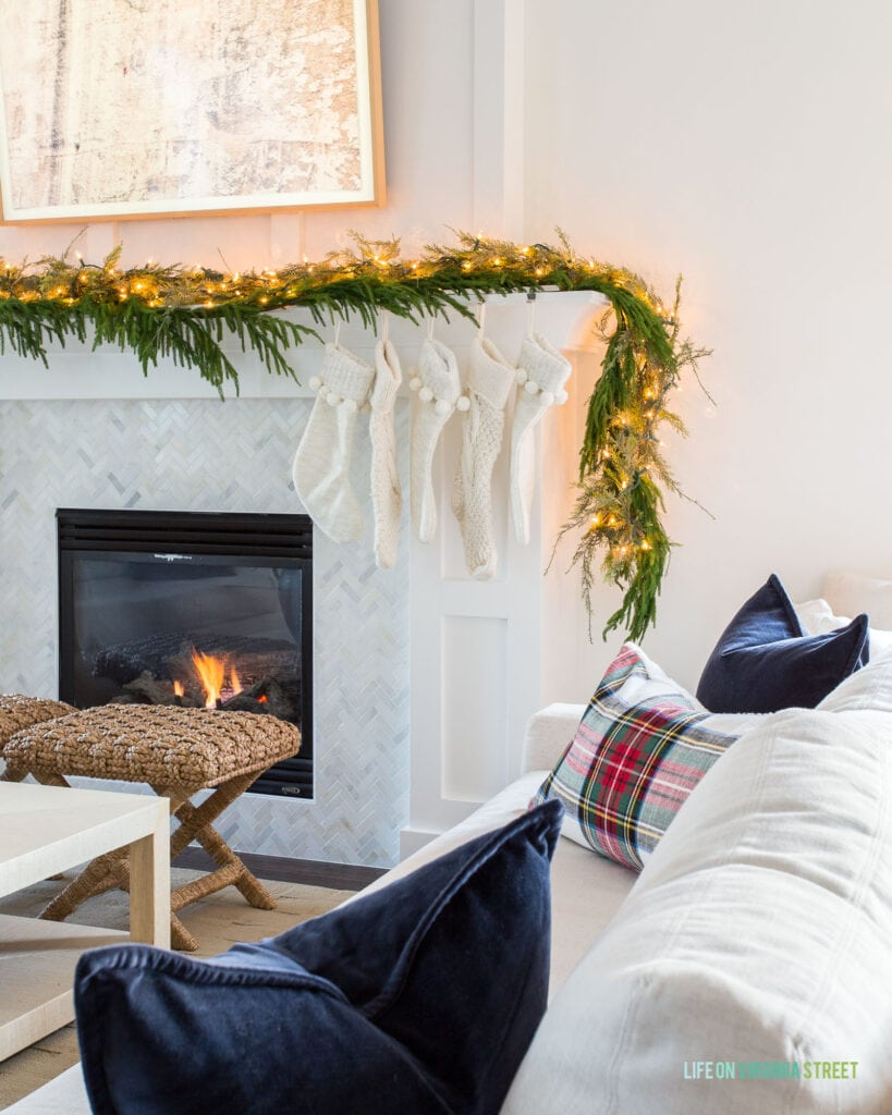 A Christmas mantel fireplace with green garland, twinkle lights, ivory woven stockings, rattan benches, and a linen sofa filled with navy blue velvet and plaid pillows.