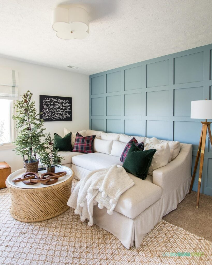 A den with a board and batten wall painted Benjamin Moore Van Courtland Blue. There is a linen sectional, bamboo coffee table, wood tripod lamp and Christmas decorations like mini Christmas trees, and plaid pillows.