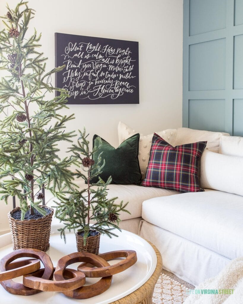 A cozy living room corner with a linen sectional, plaid pillows, a round coffee table, mini faux Christmas trees, wood link object decor, and a large 'Silent Night' canvas art piece.