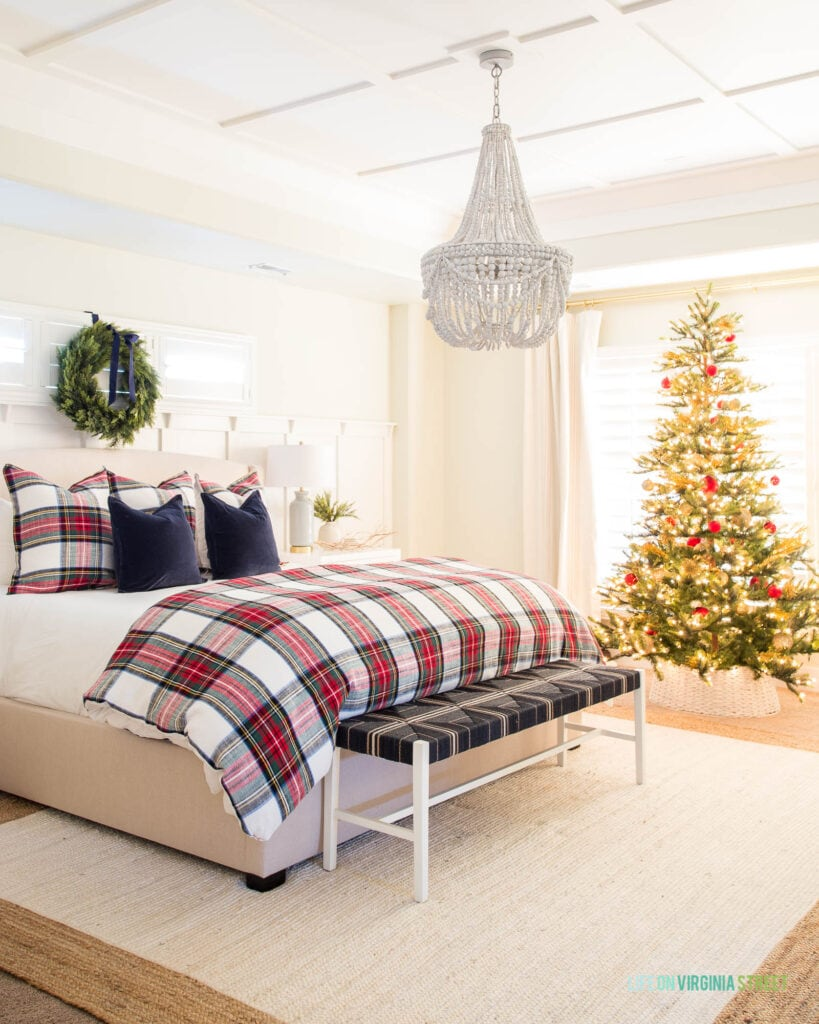 A neutral bedroom decorated for Christmas with traditional red plaid bedding, a wreath, Christmas tree with red ornaments and a wood bead chandelier.