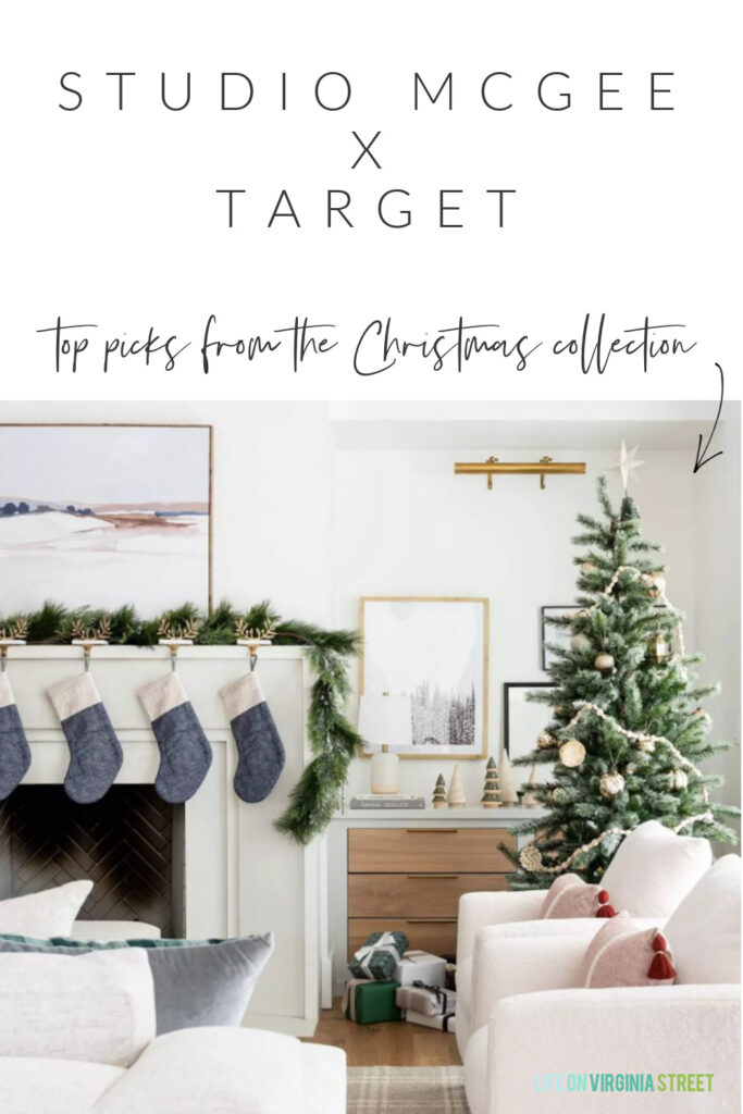 Details on the new Studio McGee Christmas collection at Target. A beautiful white living room with garland on the white limestone mantel, with abstract art, blue colorblock stockings, a plaid rug and Christmas tree with metallic ornaments.