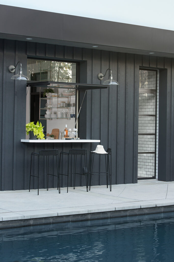 Pool house with black vertical board and batten, an outdoor bar countertop, and a dark pool.