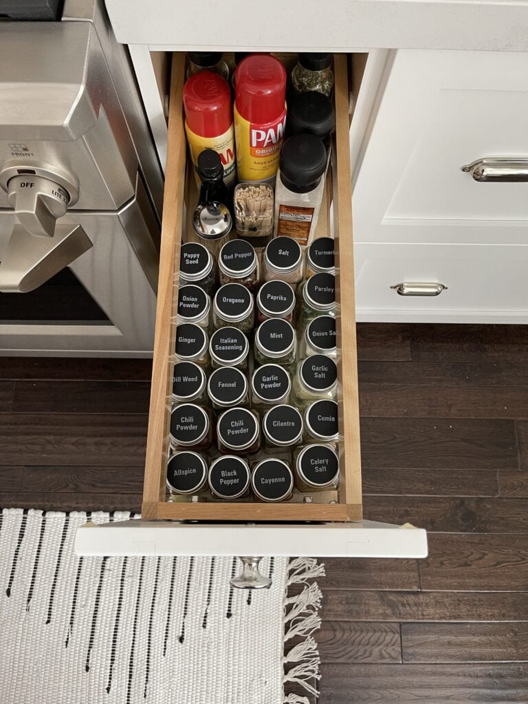 An organized spice drawer with spice jars labeled on the lid for easy viewing.