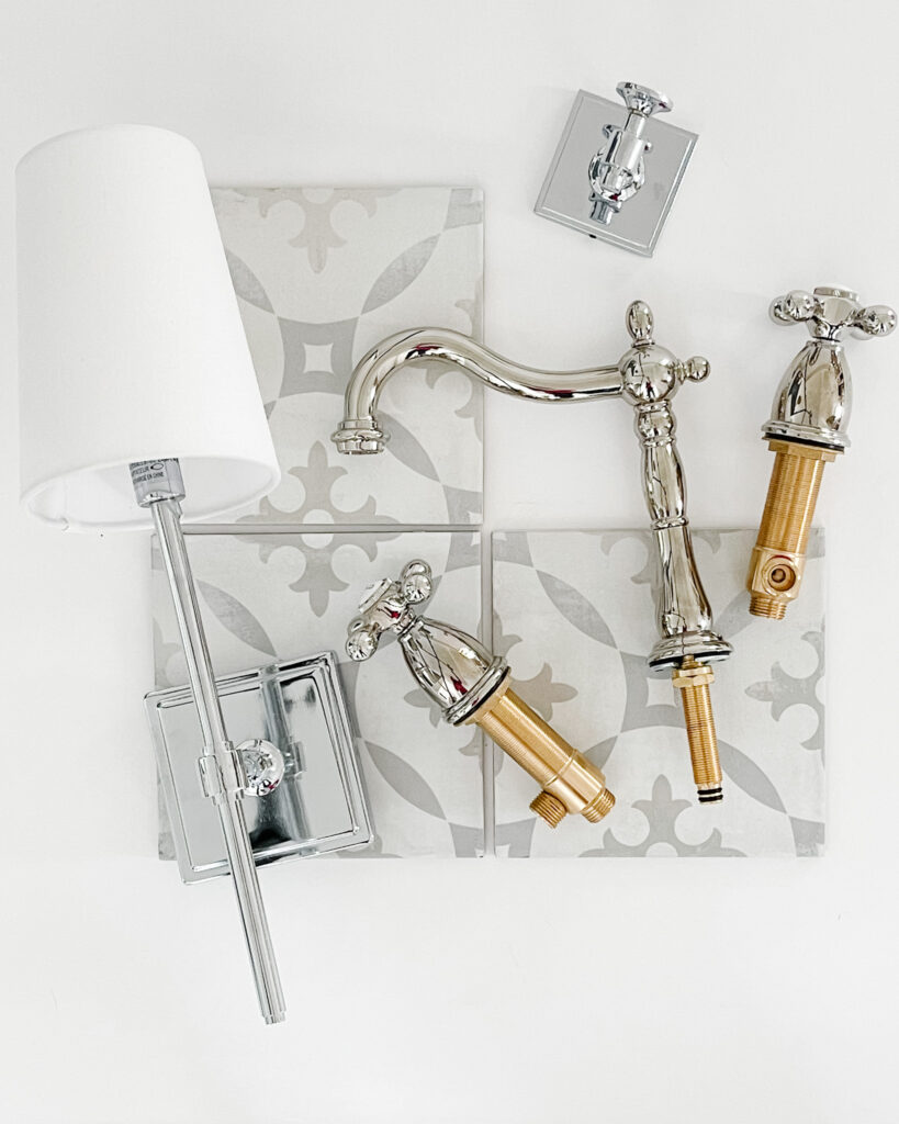A bathroom design board with a chrome bathroom sconce, patterned porcelain tile that looks like cement tile, a chrome robe hook, and vintage style bath faucets.