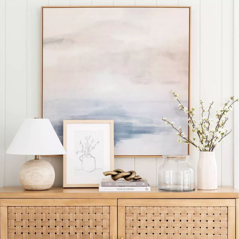 A gorgeous entryway console table vignette with pastel abstract art, a round wood lamp, metal knot decor, dogwood flowers in a vase, and a woven console table.