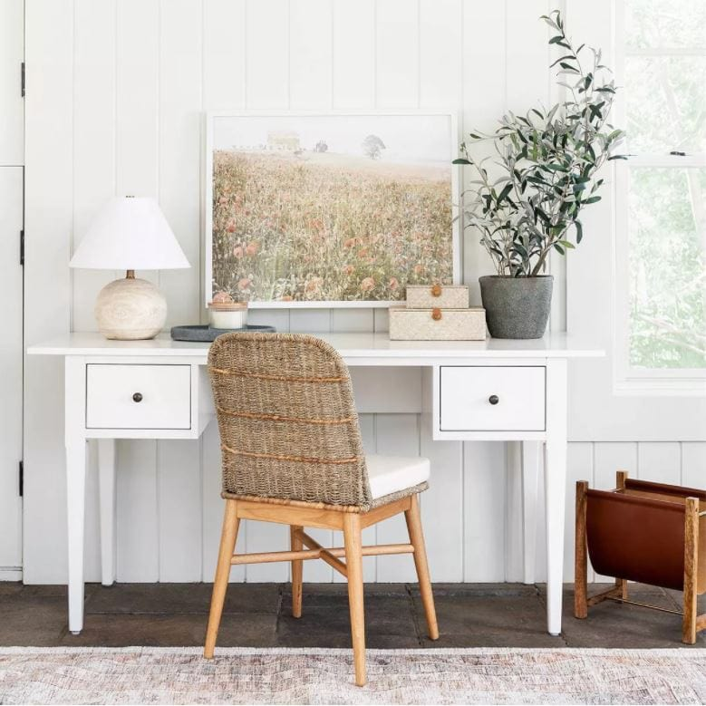 A cute white desk, woven chair, round wood lamp, wildflower art, and small olive tree in a home office space.