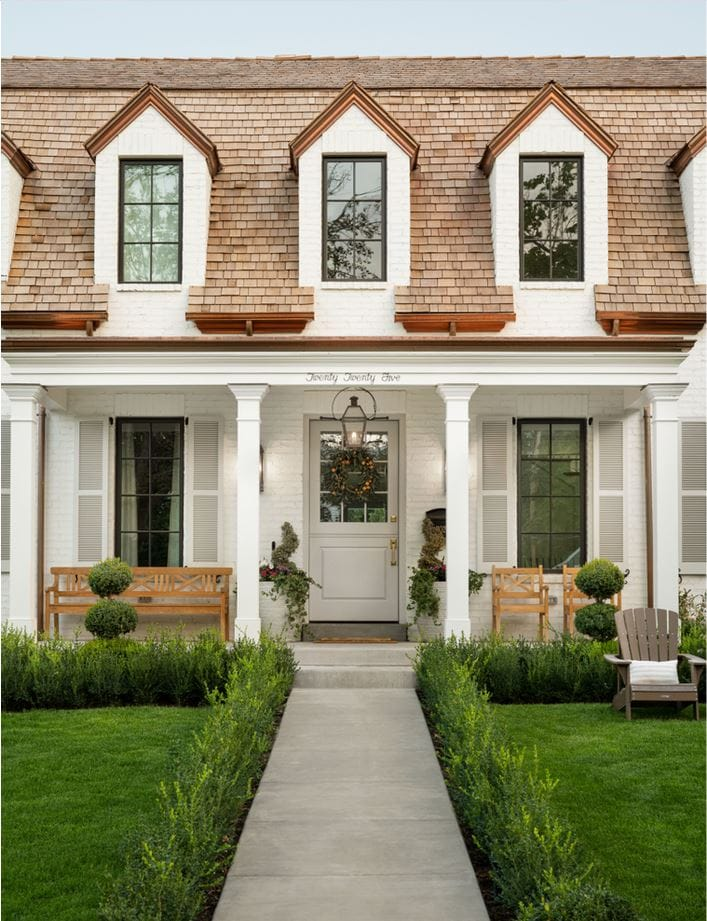 A fresh traditional white painted brick house with copper gutters and wood shingles via The Fox Group.