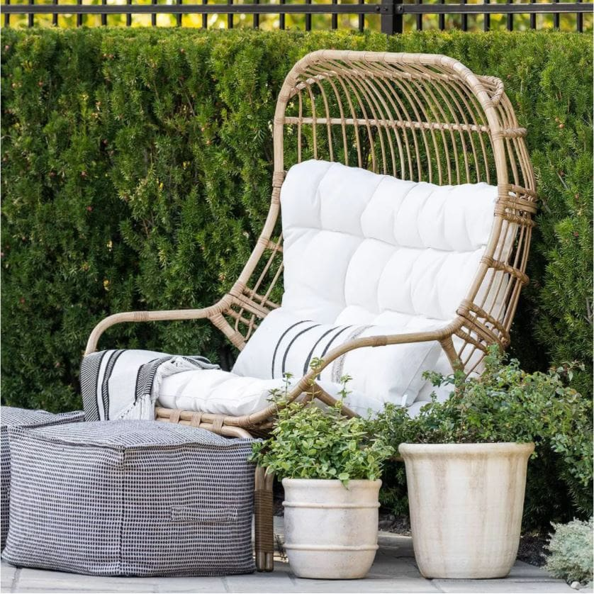 An outdoor egg chair with lumbar pillow, outdoor blanket, poufs and concrete planters from the new Outdoor dining with striped outdoor wicker chairs, an outdoor wood dining table, and outdoor place settings from the Studio McGee Threshold Patio Collection.