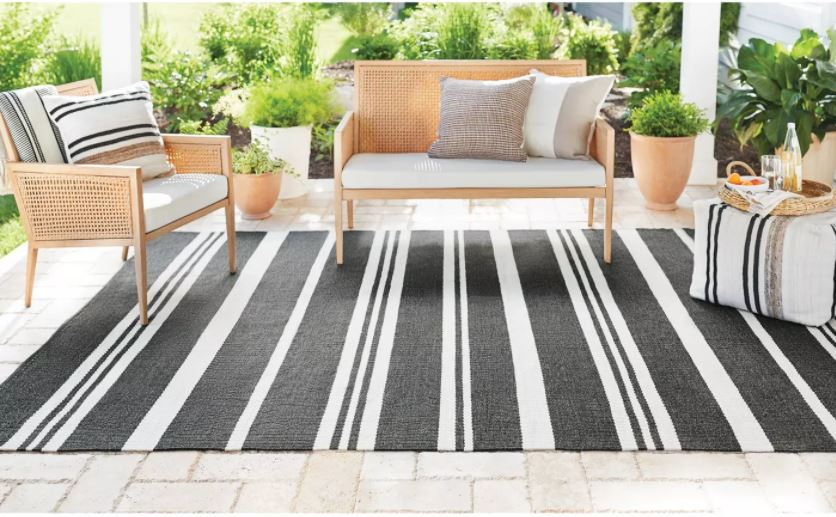 Outdoor cane inspired furniture from the new Studio McGee Target Patio Collection. Also includes a striped out door rug and outdoor poufs and planters.
