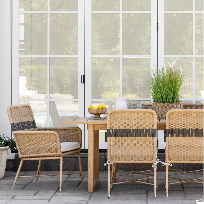 Outdoor dining with striped outdoor wicker chairs, an outdoor wood dining table, and outdoor place settings from the Studio McGee Threshold Patio Collection.