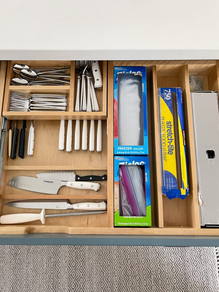 A kitchen drawer with a two levels of storage for flatware and kitchen knives. Also stores cling wrap, foil and baggies.