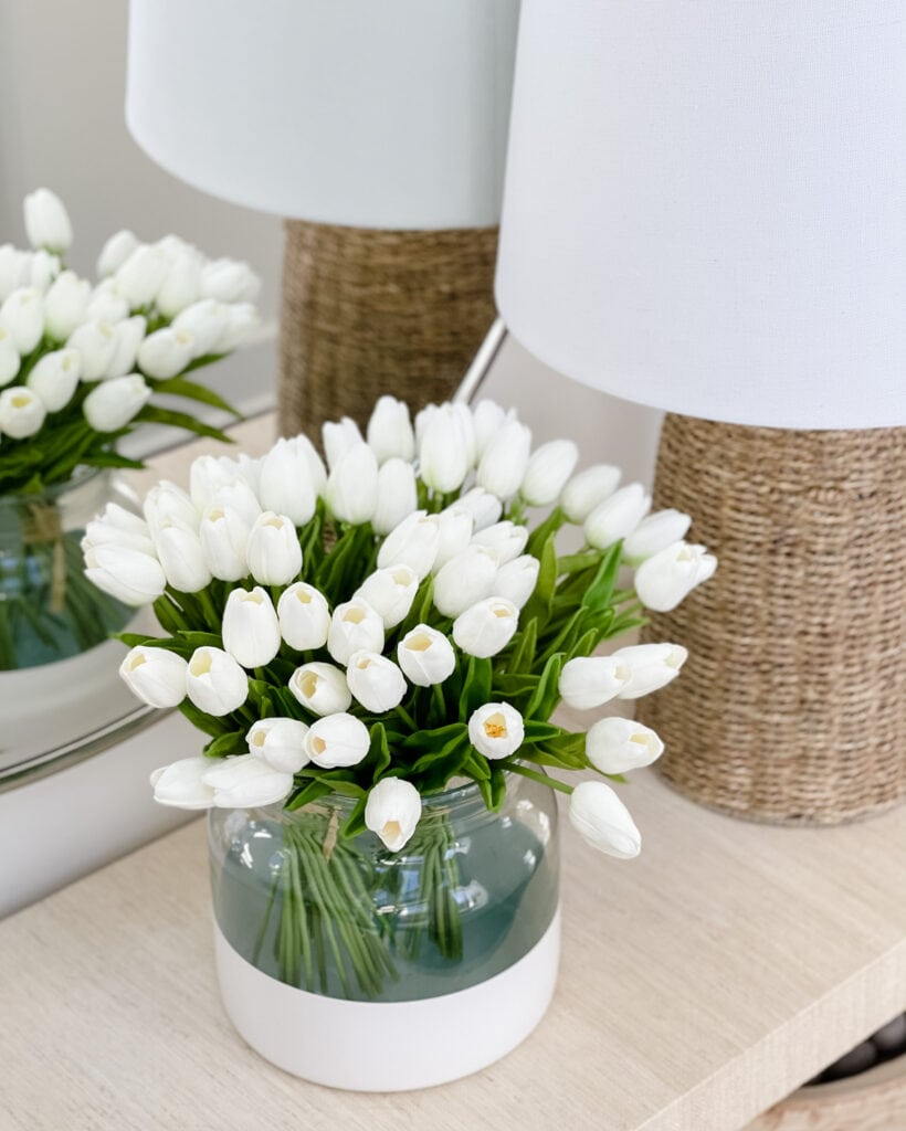 Faux white tulips in a paint dipped vase on a raffia console table. Includes other spring decorating ideas that are available on Amazon!