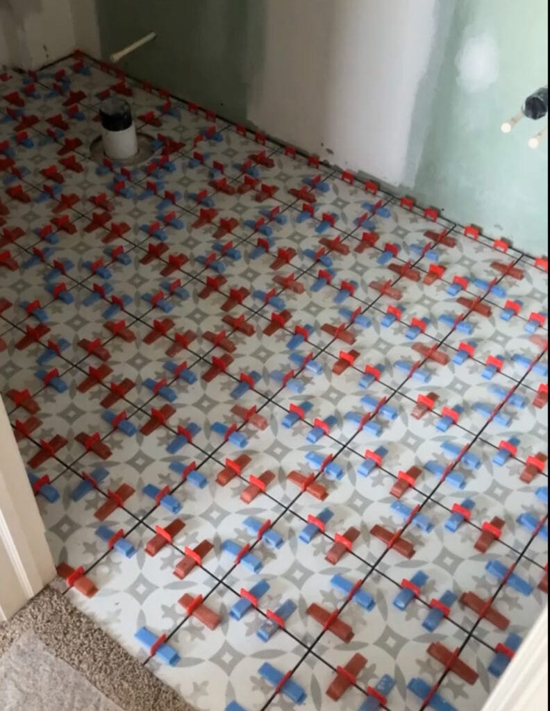 A porcelain tile floor with large spacers during installation.