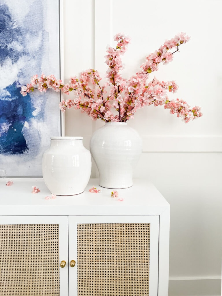 Spring decorating ideas in a home office including faux cherry blossom stems in a large white urn on a white enamel and cane cabinet.