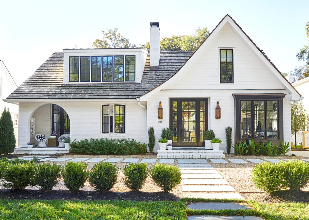 White painted brick home with black window trim, copper lanterns and an arched porch.