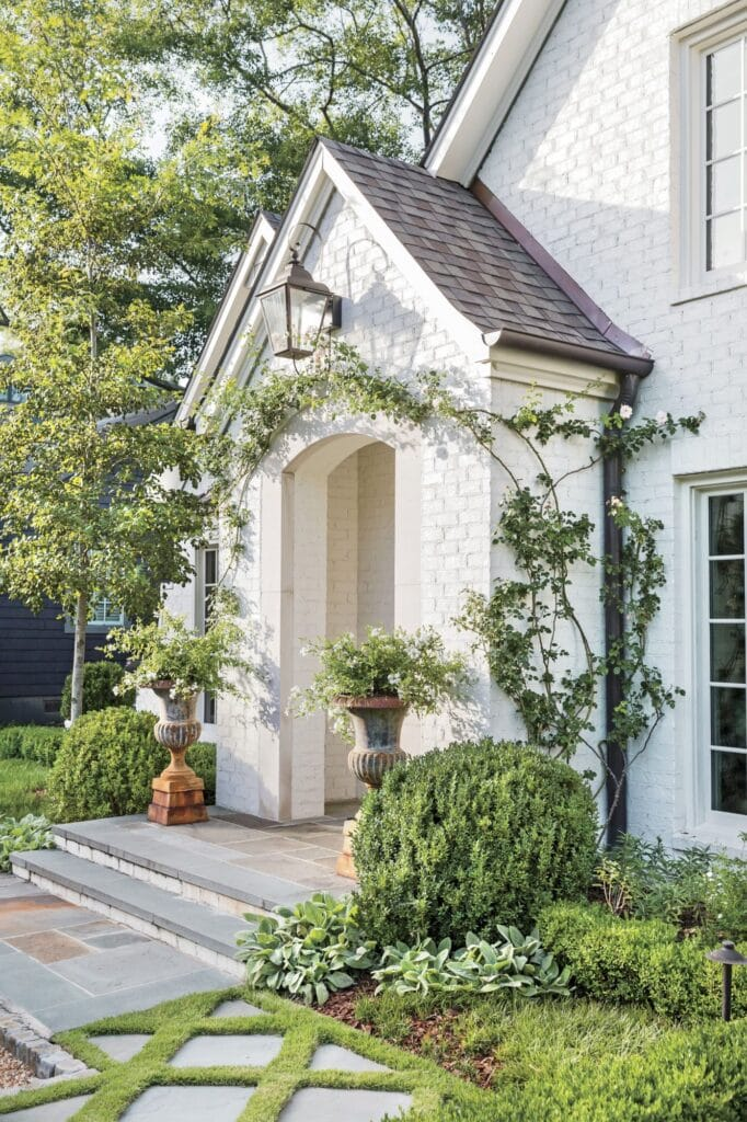 A white painted brick house exterior with brown roof, green climbing plants and white window trim.