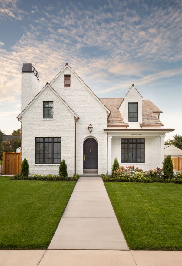 A Tudor exterior with white painted brick, black window trim, copper downspouts and a black arched front door.